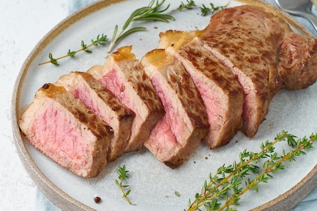 ケトケトジェニックダイエットビーフステーキ、白地にグレーのプレートにストリップロイン。パレオフードレシピ Premium写真