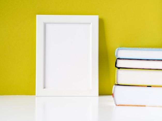 空白の白いフレームとコピースペースを持つオリーブ色の壁に対して白いテーブルの上の本のスタック Premium写真