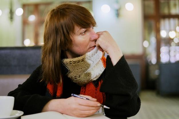 カフェの女性は、日記、弾丸ジャーナルに書き込みます。 Premium写真