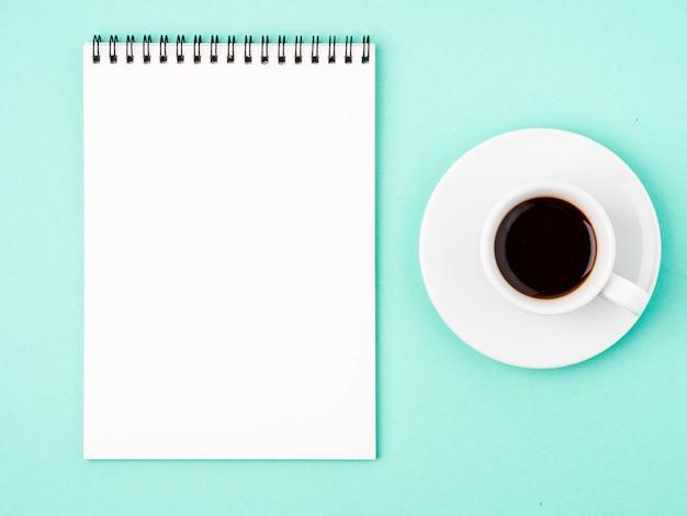 メモ帳のアイデアややることリスト、青い背景にコーヒーを書くための白い空白のページで開く Premium写真