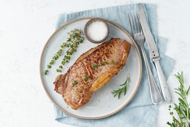 ケトケトジェニックダイエットビーフステーキ、白の灰色のプレートにストリップロイン。 Premium写真