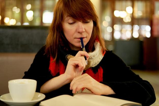 カフェの女性が日記に書く Premium写真