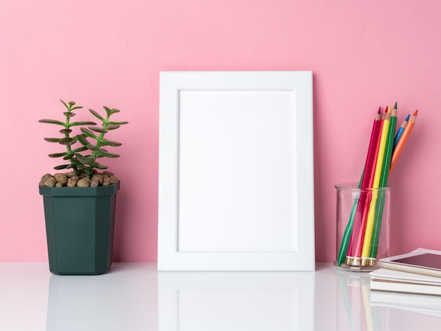 空白の白いフレーム、瓶の中のクレヨン、ピンクに対して白いテーブルの上の植物サボテン Premium写真