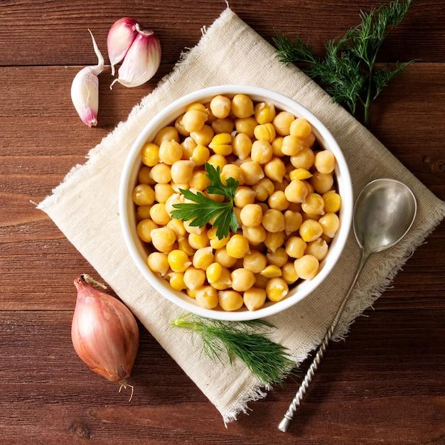 暗い木製のテーブルの上にボウルに調理されたひよこ豆。健康、菜食主義 Premium写真