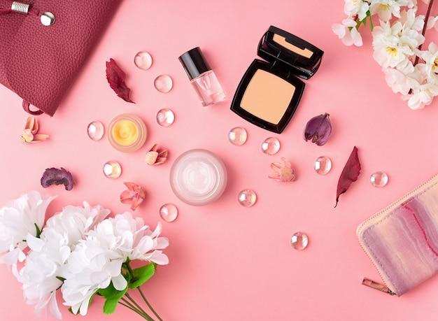 化粧品、フェイシャルクリーム、バッグ、明るいピンクのテーブルの上に花を持つフラットレイアウト女性アクセサリー Premium写真