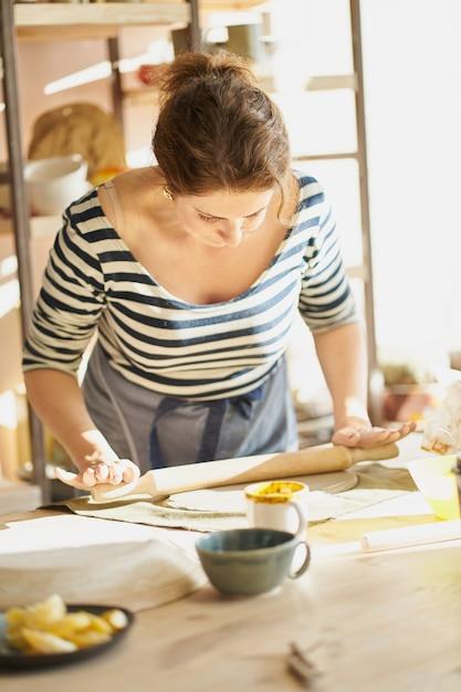 Красивая женщина, делая керамические изделия на рабочем месте в свете солнца. концепция для женщины Premium Фотографии