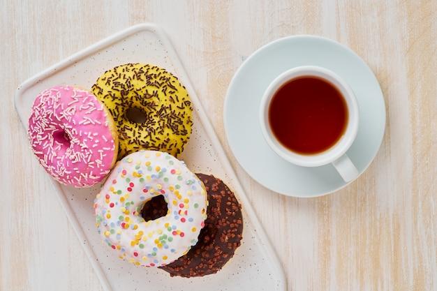 ドーナツとお茶。明るくカラフルなジャンクフード。ライトベージュの木製の背景。上面図。 Premium写真