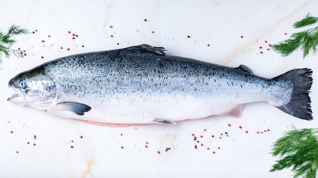 調味料、塩、唐辛子、白い大理石のテーブルにディル、トップビューで完全な新鮮な生の大きなサーモン魚 Premium写真