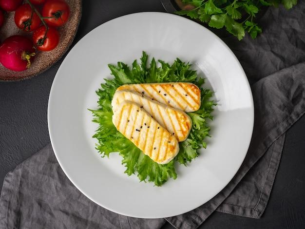 Жареный халлуми, жареный сыр с салатом. сбалансированная диета, белая тарелка на темном Premium Фотографии