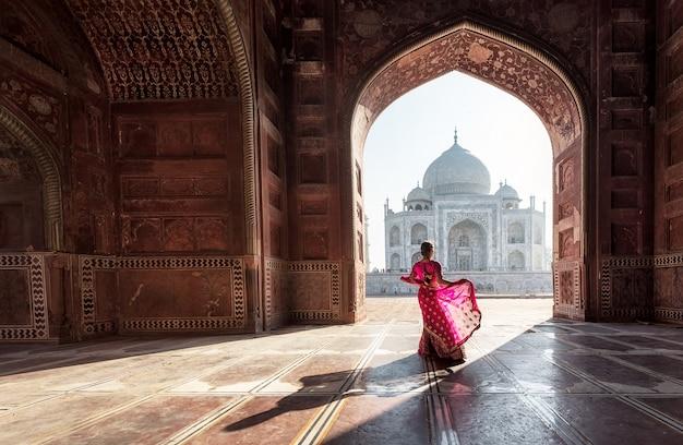 タージ・マハル、アグラ、ウッタル・プラデシュ、インドの赤いサリー/サリーの女性 Premium写真