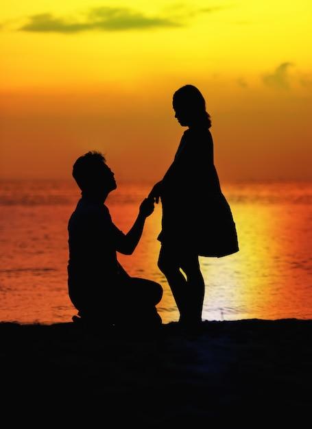 妊娠中のカップル、ビーチで夕日のシルエット Premium写真