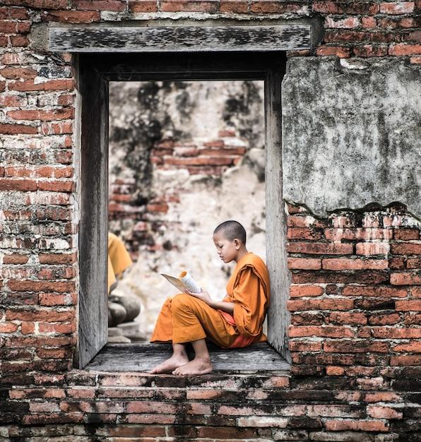 東南アジア初心者の修道士、修道院の外の本を読んで、仏教の教え。 Premium写真