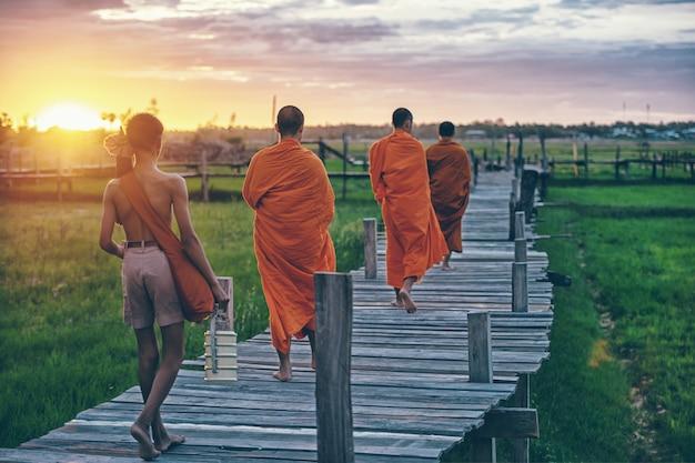 Буддийские монахи на милостыню ежедневного утра традиционные в таиланде. Premium Фотографии