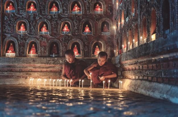 Молодые монахи новичка освещая свет горящей свечи внутри буддийского виска, установку нижнего света, положение шани, мьянму. Premium Фотографии