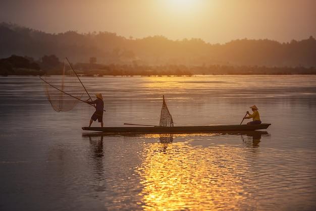 タイの田舎で日の出の背景に漁師 Premium写真