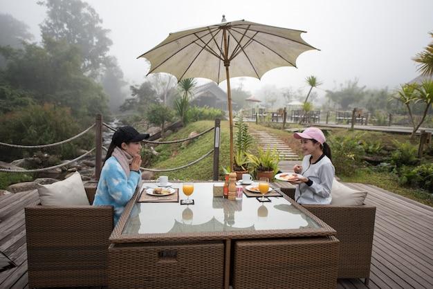朝の朝食テーブルでアジアの女性。 Premium写真
