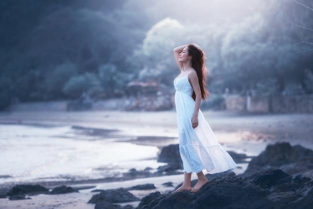 Свободная счастливая женщина на пляже, наслаждаясь природой. Premium Фотографии