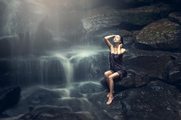 美しいアジアの女性の滝 Premium写真