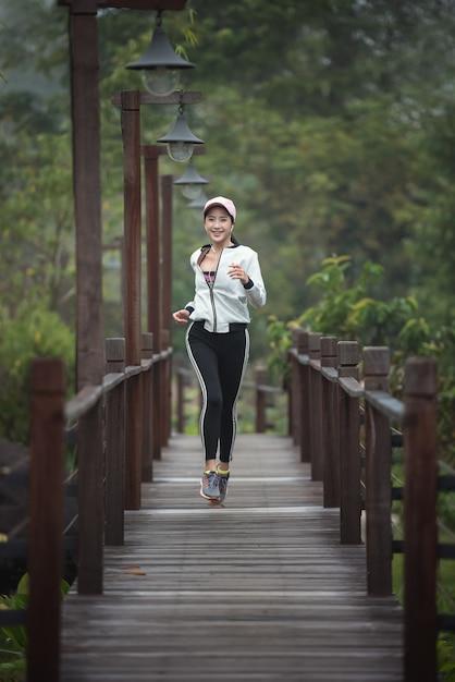 Молодая женщина работает на деревянный мост Premium Фотографии