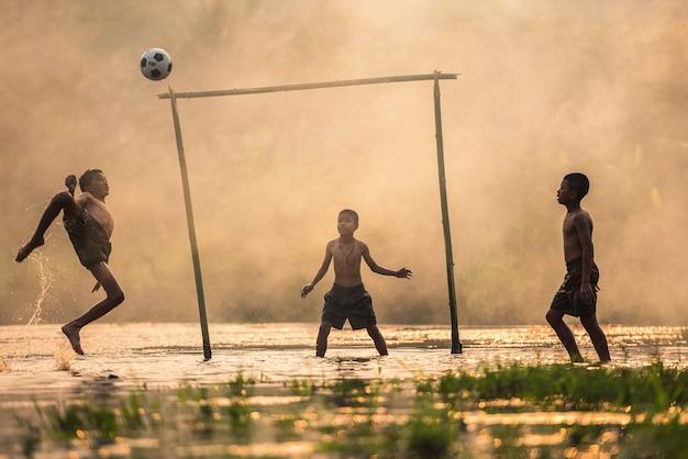 サッカーボールを蹴る少年 Premium写真