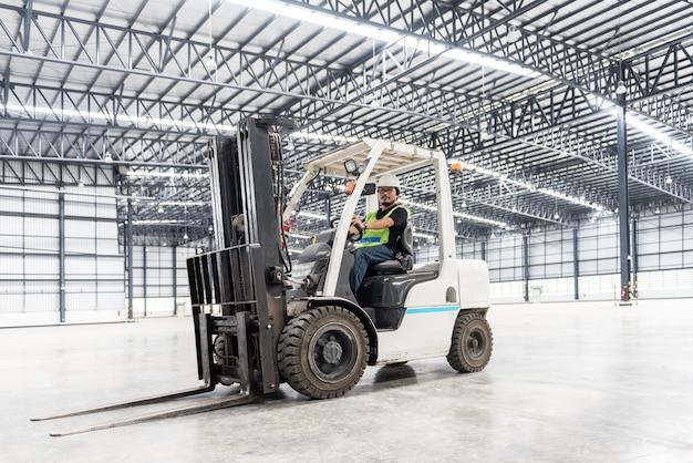 倉庫の倉庫で制服を着た倉庫労働者ドライバー Premium写真