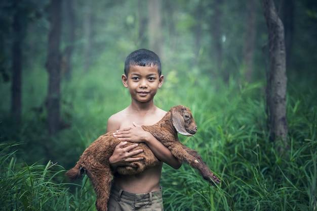 アジアの少年が牧草地でヤギの赤ちゃんと一緒に保持しています。 Premium写真