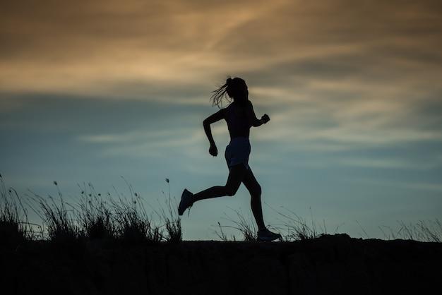 トレイルで実行されているランナーの運動選手。女性フィットネスジョギングワークアウトウェルネスコンセプト。 Premium写真