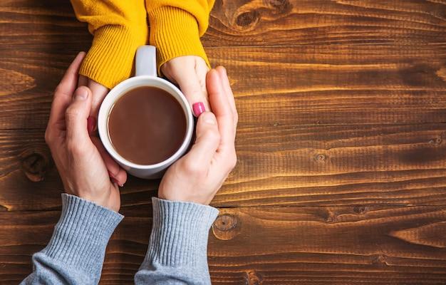 Чашка напитка на завтрак в руках влюбленных. Premium Фотографии
