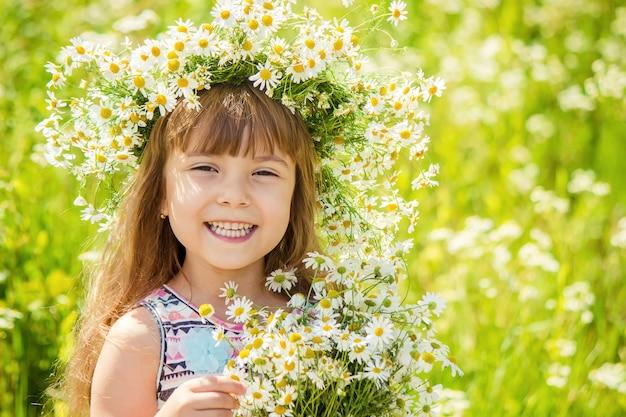 カモミールを持つ少女。セレクティブフォーカス自然の花。 Premium写真