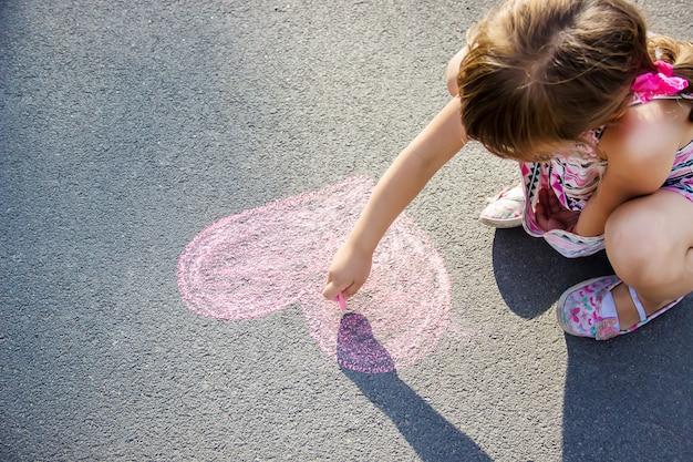 子供はアスファルトの心にチョークを塗ります。セレクティブフォーカス Premium写真