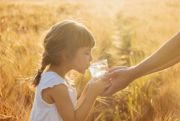 父親は子供にコップ一杯の水を与えます。セレクティブフォーカス Premium写真