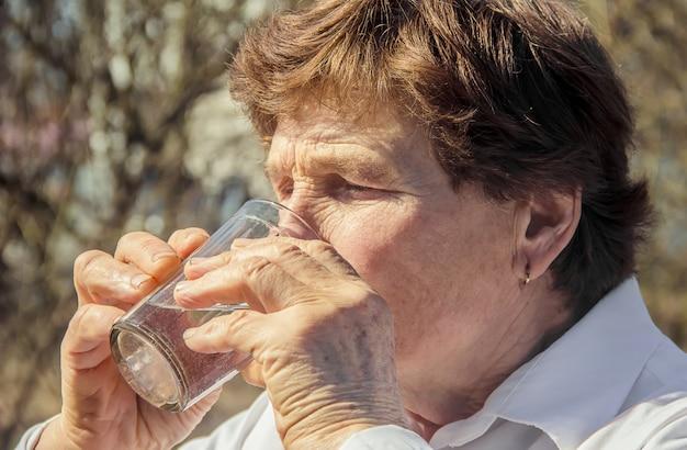 祖母は子供に一杯のきれいな水を与えます。セレクティブフォーカス Premium写真