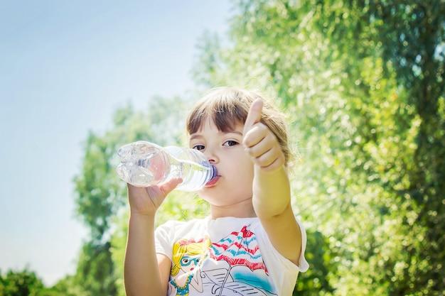 Ребенок пьет воду из бутылочки. выборочный фокус. Premium Фотографии