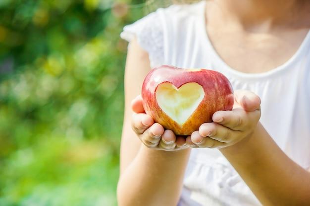 Ребенок с яблоком. выборочный фокус. сад. Premium Фотографии