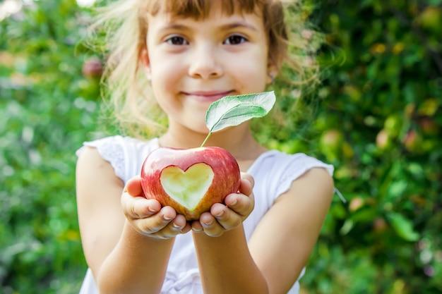 りんごを持つ子供。セレクティブフォーカス庭園。 Premium写真