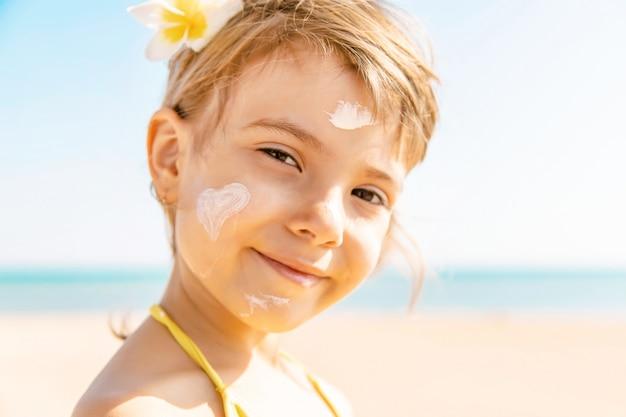 Ребенок на пляже мажет солнцезащитный крем. выборочный фокус. Premium Фотографии