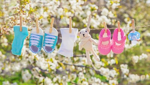ベビー服やアクセサリーは戸外で洗った後、ロープで重さを量る。セレクティブフォーカス Premium写真