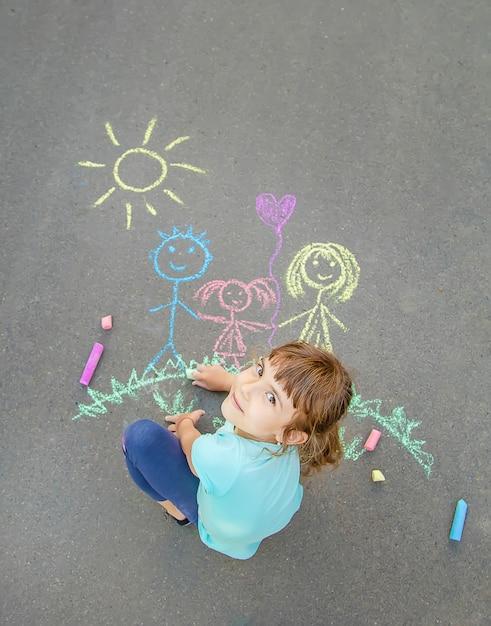子供はチョークで歩道に家族を描きます。セレクティブフォーカス Premium写真