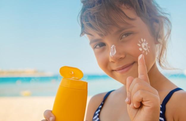 Солнцезащитный крем на коже ребенка Premium Фотографии