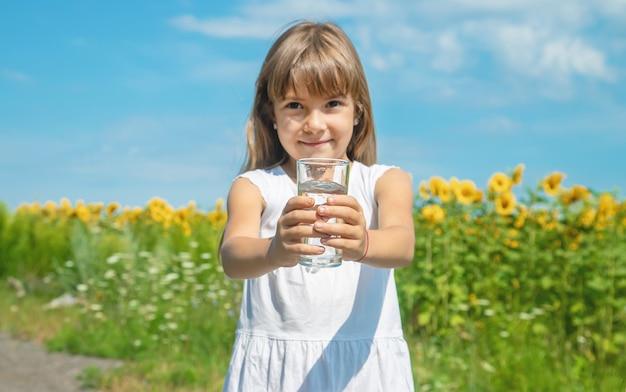 子供がフィールドの背景に水を飲む Premium写真