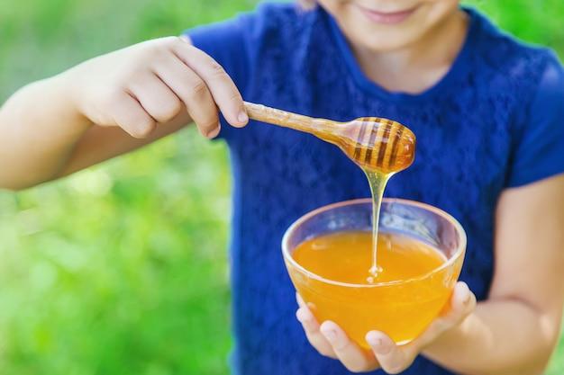 子供の手に蜂蜜のプレート Premium写真