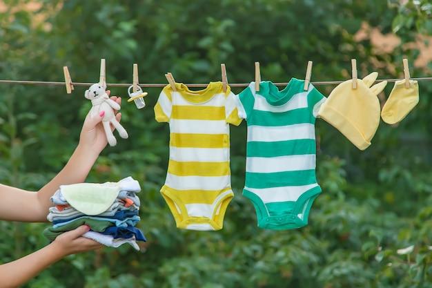 ベビー服を洗う、リネンは新鮮な空気で乾く Premium写真