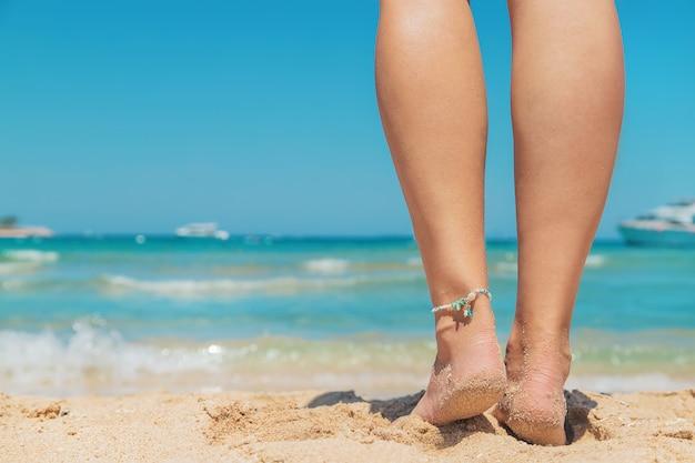Ноги девушки на берегу моря Premium Фотографии