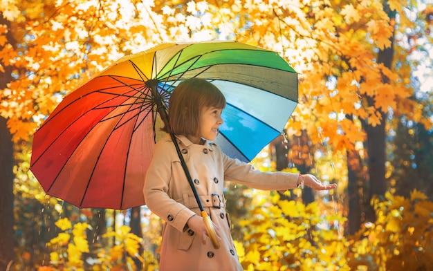 秋の公園で傘の下の子。セレクティブフォーカス。 Premium写真