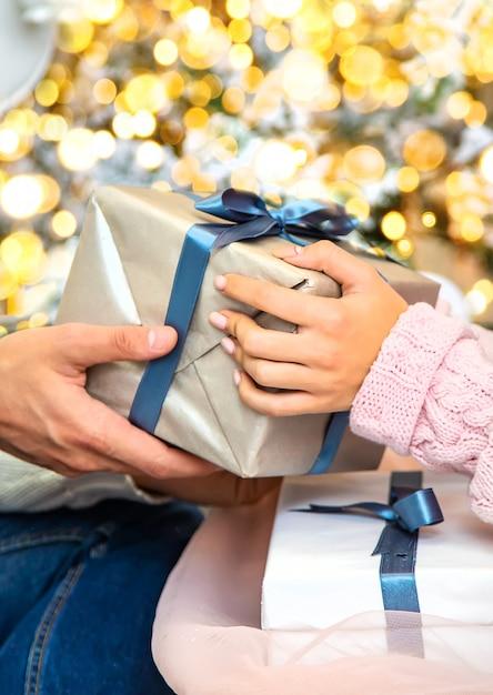 クリスマスは男性と女性の手にプレゼントされます。セレクティブフォーカス。 Premium写真