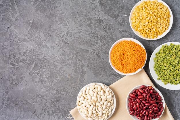 エンドウ豆、レンズ豆、豆、豆類の灰色の背景上の品揃えの平面図です。 Premium写真