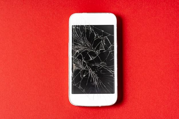 赤の背景にひびの入った表示で壊れた携帯電話。 Premium写真