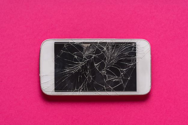 紫色の背景にひびの入った表示で壊れた携帯電話。 Premium写真