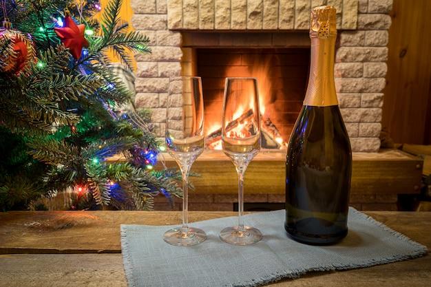 Рождественский сочельник. два бокала шампанского вина возле уютного камина и перед рождественской елкой украшали игрушки и рождественские огни в загородном доме. Premium Фотографии