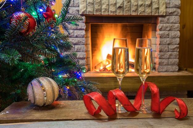 クリスマス・イブ。カントリーハウスでクリスマスツリー装飾おもちゃやクリスマスライトの前に居心地の良い暖炉の近くのテーブルの上のシャンパンワイン。 Premium写真